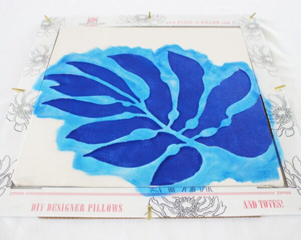 Painting the stencil of blue leaf:If you want to add some coastal charm to your home. Learn learn how to easily stencil a large tropical leaf on a pillow.