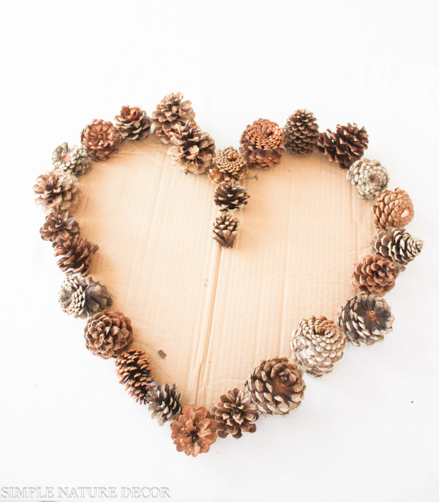 Filling the valentines day wreath with pinecones
