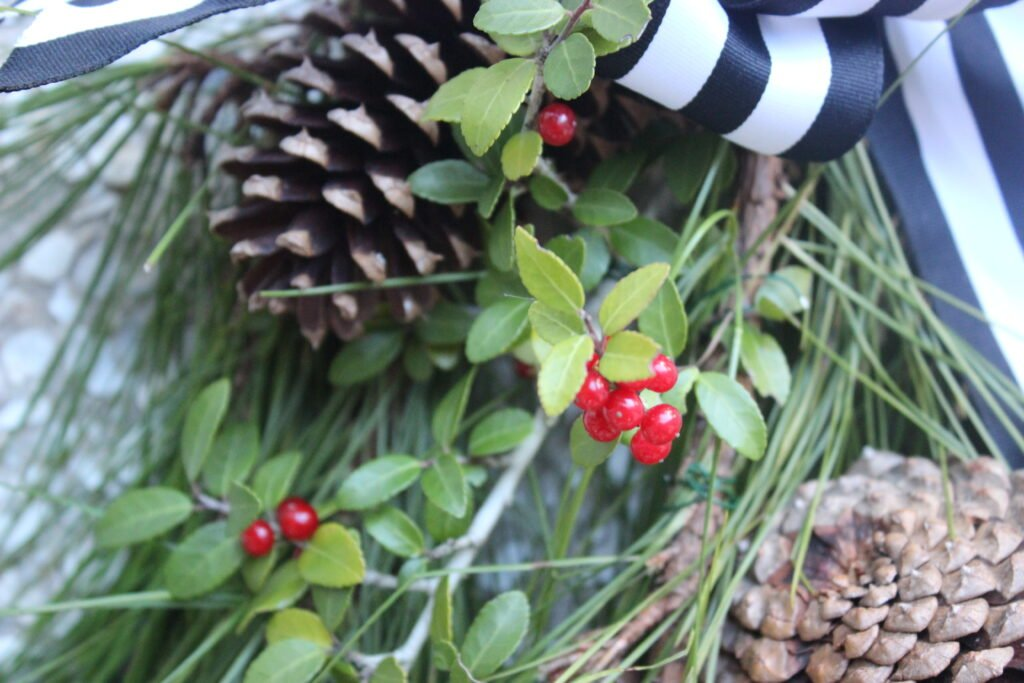 Red berries and pinecones: How To Make Christmas Evergreen Swag Wreath