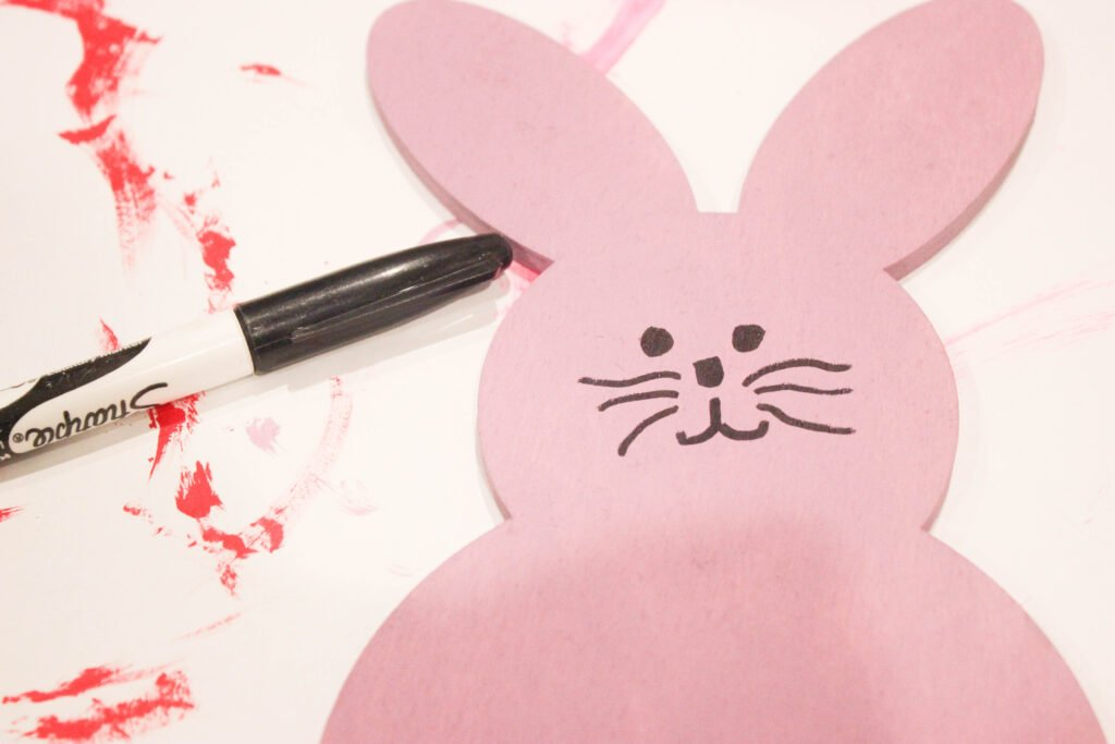 drawing a face on wooden easter bunnies
