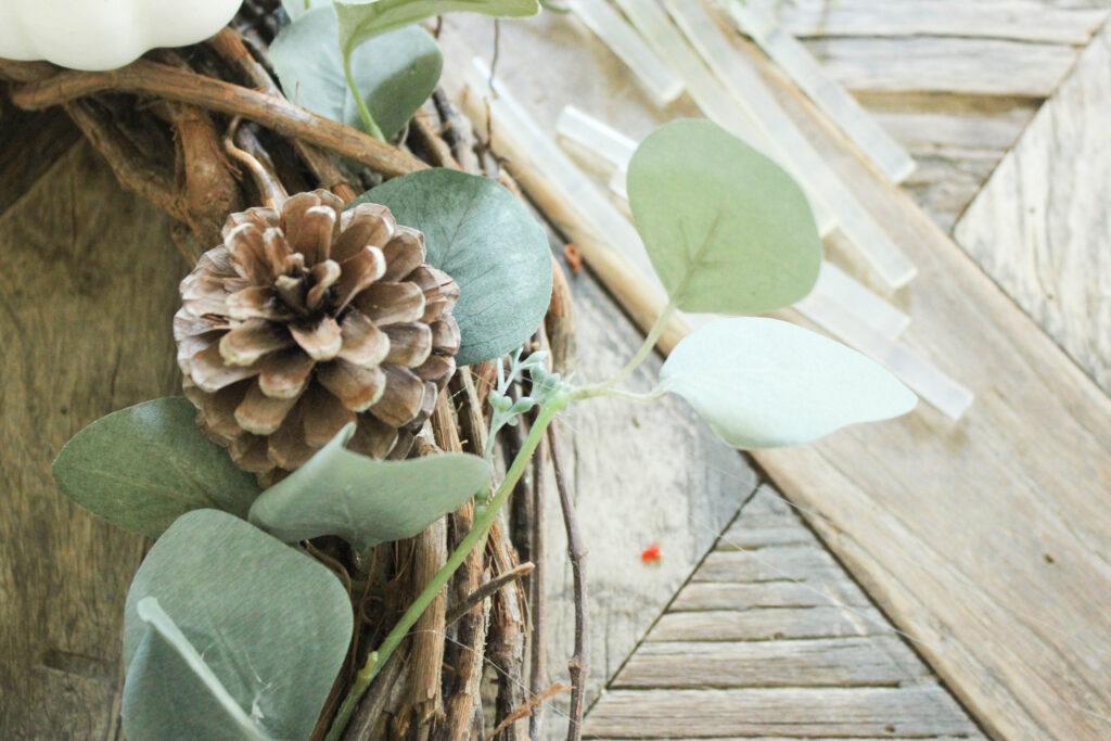 Add pinecones:white pumpkin wreath